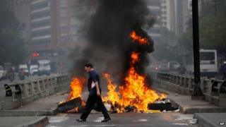 A pedestrian walks in front of a burning barricade blocking the highway in Chacao, Caracas, on 24 February, 2014