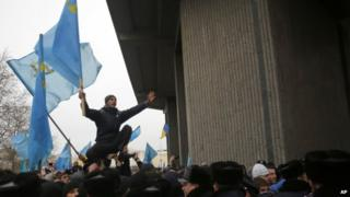 A Crimean Tatar shouts slogans and waves the ethnic flag of the Crimean Tatars during a protest in front of a local government building in Simferopol, Crimea, Ukraine, Wednesday, Feb. 26, 2014.