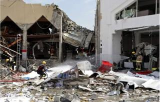A fire fighter sprays the site at a Turkish restaurant following a suspected gas explosion in Doha