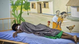 A newly-diagnosed HIV positive woman lies in the treatment ward of the Mildmay Uganda clinic on 27 February