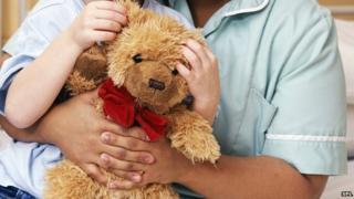 A teddy bear being cuddle by child and nurse
