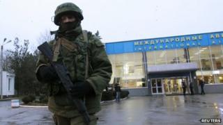An armed man patrols outside the airport in Simferopol, Crimea
