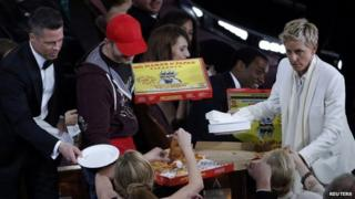 Ellen DeGeneres gives out pizza to the glittering audience, including Brad Pitt