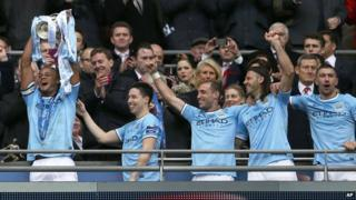 Manchester City players celebrate with Capital One trophy