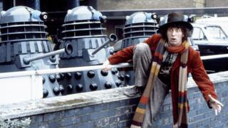 Tom Baker as the Doctor, with Daleks in TV Centre car park