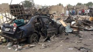 People gather on 2 March 2014 near a car which had exploded in the city of Maiduguri in northern Nigeria