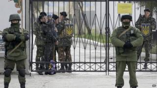 A Ukrainian soldier with a child 2nd left, watches Russian soldier guard the gate of an infantry base in Perevalne, Ukraine,
