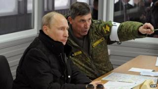 Russian President Vladimir Putin (left) listens to the head of the Russian army's main department of combat preparation Ivan Buvaltsev in the Leningrad region on 3 March 2014