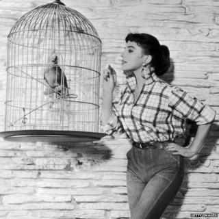 Joan Collins with bird in a cage