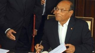 Tunisian President Moncef Marzouki reacts as he signs the new Constitution in Tunis (27 January 2014)