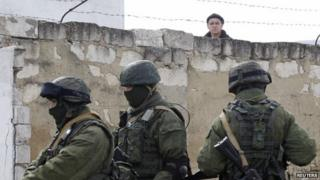 A Ukrainian serviceman (rear) looks at uniformed men, believed to be Russian servicemen, standing guard at a Ukrainian military base in a village outside Simferopol, Crimea, 6 March 2014