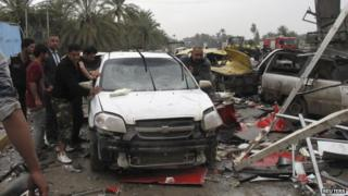 People push a damaged car at the scene of a suicide attack in the city of Hilla, 9 March