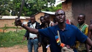 An Anti-Balaka fighter, member of a militia opposed to the Seleka rebel group, lifts up a machete threatening any Seleka that may attack, on the outskirts of the Boy-Rabe neighborhood in Bangui on December 14, 2013