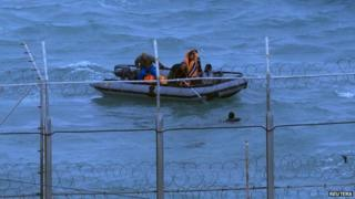 Moroccan soldiers remove a migrant from the water near Ceuta's border fence