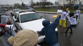 A Tacoma Police Officer uses his vehicle to move Enrique Agular out of the way as protesters block the road in front of the federal Northwest Detention Center 24 February 2014