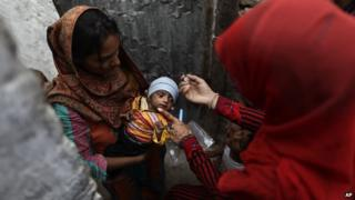 Pakistani health worker Salma Saleem, right, gives a a polio vaccine to a child, in a neighborhood in Islamabad, Pakistan