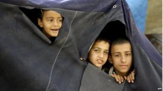 Young Palestinian refugees, who fled the Yarmouk refugee camp in Syria, peer through holes made in their tent as they prepare to move to new houses built by the United Nations Development Programme at the Palestinian refugee camp of Ain El-Helweh, near the southern Lebanese coastal city of Sidon