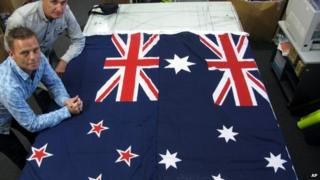 Flagmakers Victor Gizzi (L) and David Moginie pose next to flags of New Zealand (L) and Australia (R) in their factory near Wellington, New Zealand on 3 March 2014