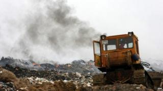 A tractor deals with burning garbage at Moscow landfill site