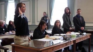High school student Rachel Canning, 18, left, takes the oath in court as her parents, Elizabeth and Sean, look on in Morris County Superior Court in Morristown, New Jersey 4 March 2014