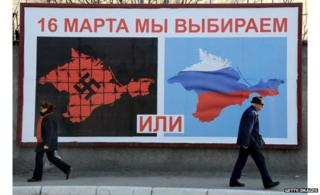 People walk past election posters in Crimea