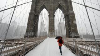 A man walks across the Brooklyn Bridge into New York in heavy snow