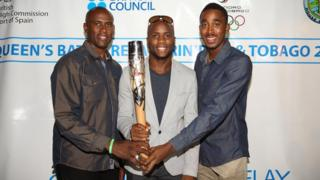 Olympic Games silver and bronze 4x100m medallist Emmanuel Callender (centre) and World Champion 400m hurdler Jehue Gordon (right) hold the Queen's Baton with Commonwealth Games silver and bronze shooting medallist Roger Daniel (left).