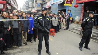 Police stand guard in front of local residents near a crime site on a street in Changsha, Hunan Province, 14 March 2014