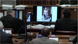 An image taken from the court pool TV via AP showing on screen a police photograph of Oscar Pistorius standing on his blood-stained prosthetic legs and wearing shorts covered in blood, taken shortly after the athlete fatally shot his girlfriend, which was shown to the court in Pretoria, at his murder trial Friday, March 14, 2014.