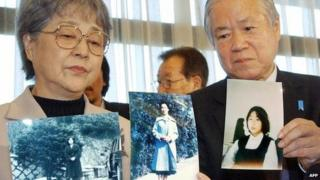 Shigeru and Sakie Yokota show portraits of their daughter Megumi at a press conference in Tokyo on 16 November 2004