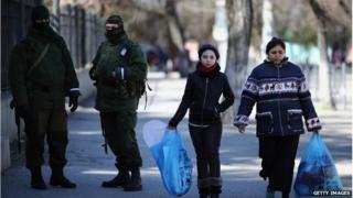 Members of the public walk past pro-Russian troops in Simferopol, Crimea (17 March 2014)