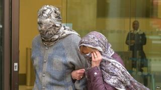 Domenico Rancadore and his wife hide their faces as they are perused by journalists