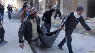 Men carry the body of an executed detainee found at a children's hospital occupied by the Islamic State in Iraq and the Levant (ISIS) in Aleppo (8 January 2014)