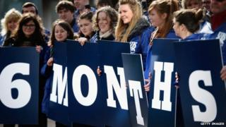 Children holding six-months-to-go signs