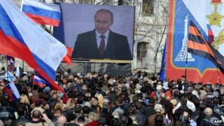 People listen to a speech of Russian president Vladimir Putin broadcast on a giant screen in Sevastopol