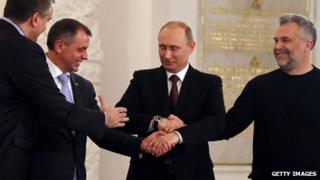 Vladimir Putin, centre, joins hands with three Crimean leaders