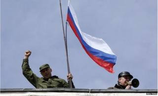 A man holds a Russian flag on the roof of the naval headquarters in Sevastopol on 19 March 2014