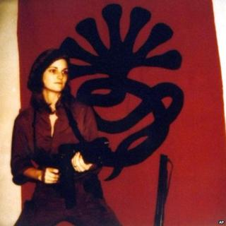 Patty Hearst in front of the Symbionese Liberation Front logo