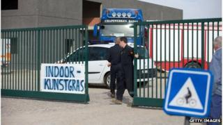 A man closes the gate to an industrial site where a World War One shell exploded during excavation works