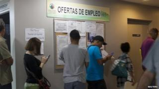 People line up at an unemployment office of the Labor Department in San Juan March 13, 2014.
