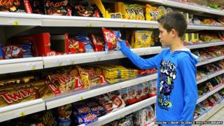 Boy being tempted by chocolates in a supermarket