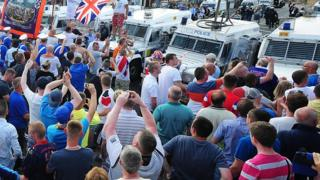 A large crowd gathered in the Woodvale area of north Belfast to protest against a 12th July parade ruling