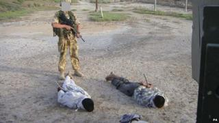 The Al-Sweady Inquiry undated handout image of detained Iraqis being guarded by a British soldier .