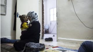 Syrian woman and child in room in Zarqa (file photo)