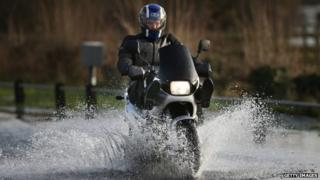 Motorcyclist riding through floodwater in Chertsey