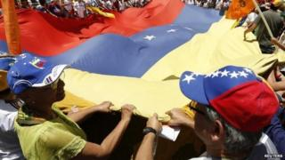 Opposition supporters hold a national flag in Caracas, Venezuela. Photo: 22 March 2014