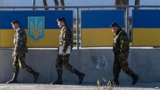 Russian officers walk past the Ukrainian marine battalion headquarters in Feodosia (23 March 2014)