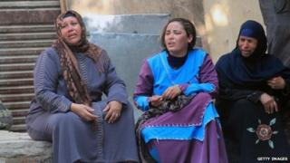 Egyptian relatives of supporters of ousted president Mohamed Morsi cry sitting outside the courthouse in the central Egyptian city of Minya