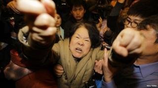 A family member of a passenger on board Malaysia Airlines MH370 shouts at journalists after watching a television broadcast of a news conference, at the Lido hotel in Beijing, on 24 March 2014