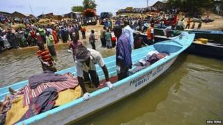 Volunteers prepare to carry the bodies of people killed after a boat disaster on Lake Albert in Uganda (24 March 2014)